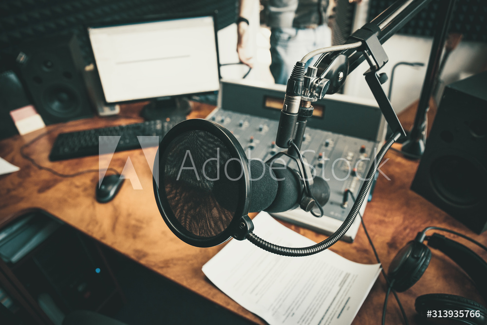 Radio station microphone in recording studio or broadcast room, working place of radio host, close up.
